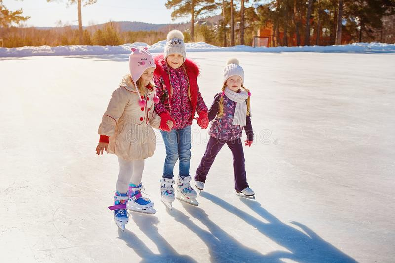 Three little girls skate on the ice. Vacations and holidays in nature royalty free stock photography