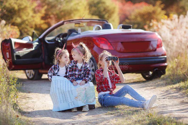 Three little girls traveling by car on a country road in the nature in summer stock photo