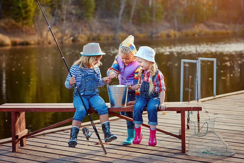 Three little happy girls brag about fish caught on a fishing pole. Fishing from a wooden pontoon. royalty free stock image