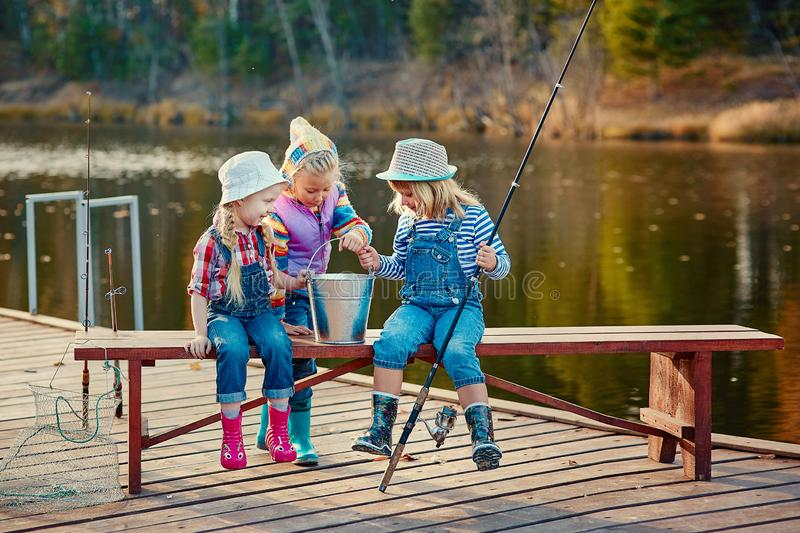 Three little happy girls brag about fish caught on a fishing pole. Fishing from a wooden pontoon royalty free stock photography