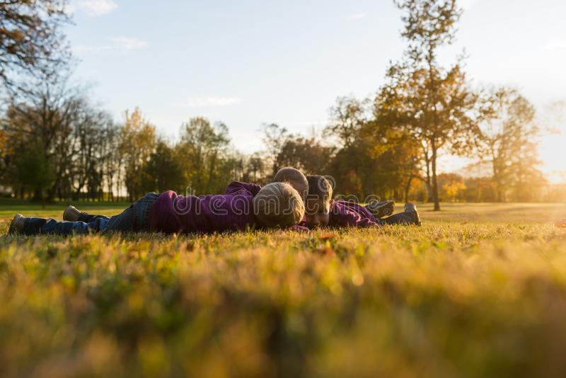 Three little kids, siblings, lying on an autumn grass royalty free stock photo