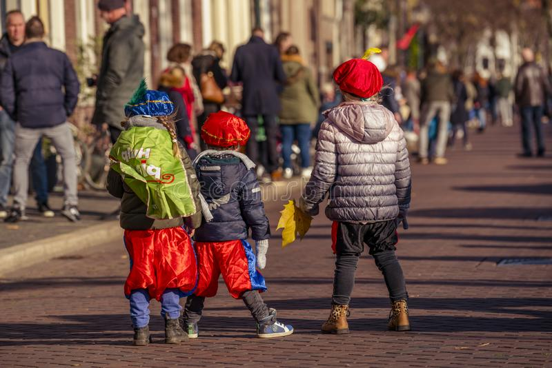 Three little kids Waiting in anticipation. Dordrecht, Netherlands - November 17, 2018: Three young children waiting in anticipation in costume for Saint Nicolaas royalty free stock photo