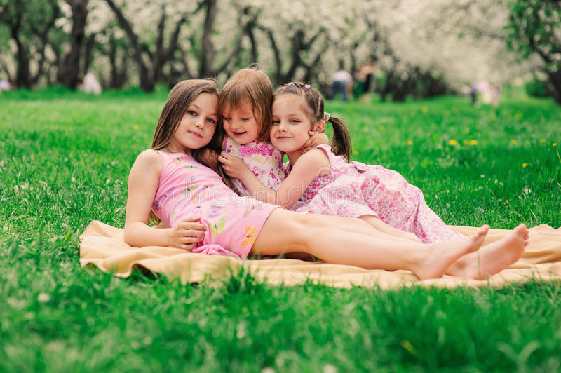 Three little sisters having a lot of fun playing together outdoor in summer park royalty free stock photos