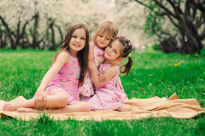Three little sisters having a lot of fun playing together outdoor in summer park stock photos