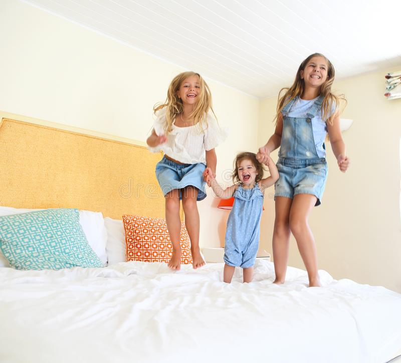 Three little sisters Jumping on a bed stock photo