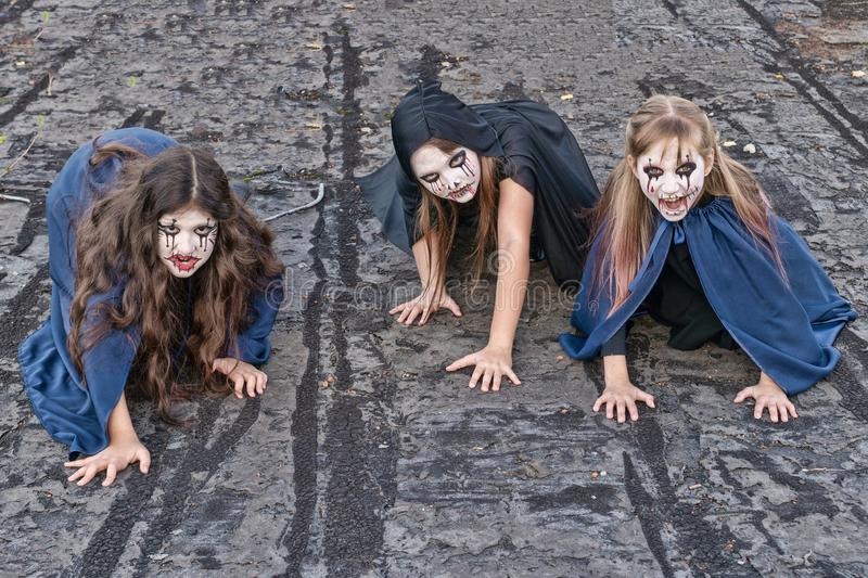 Three little teenage girls in zombie costumes crawl along the roof of an old ruined building and look frighteningly at the camera royalty free stock photography