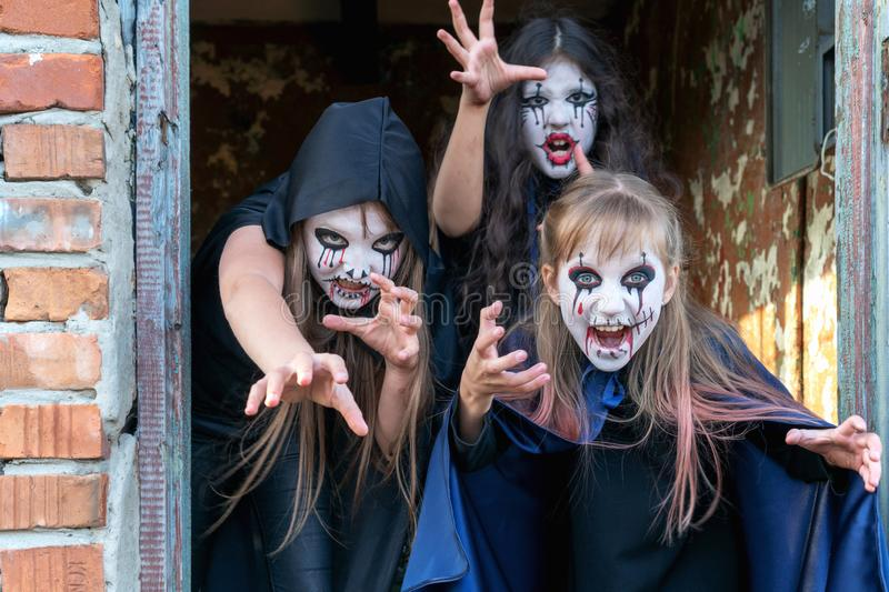Three little teenage girls in zombie costumes go out the door of an old ruined building and look frighteningly at the camera. royalty free stock photography