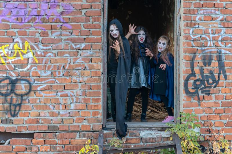 Three little teenage girls in zombie costumes go out the door of an old ruined building and look frighteningly at the camera. stock photo