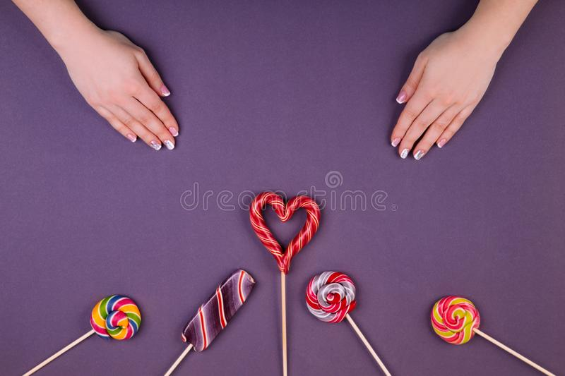Three lollypops and manicure. Concept of stylish french manicure, female manicure and lollypops,  striped lollypop looks like an ice-cream, round swirled and royalty free stock photo