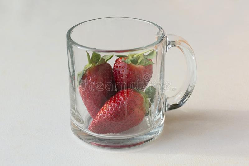 Three Luscious Strawberries in a Mug royalty free stock photography