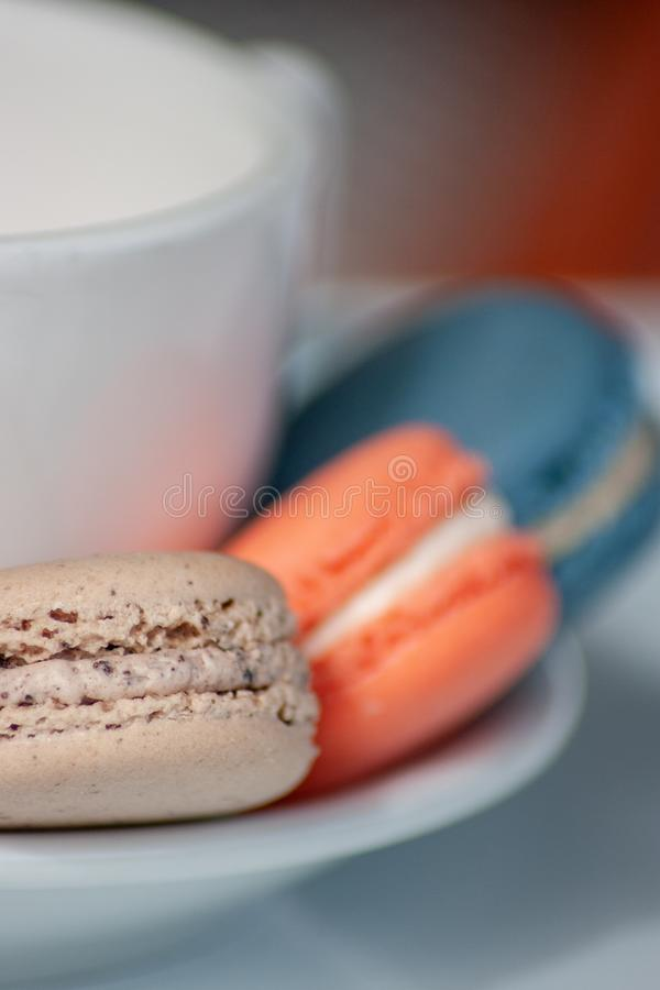 Three Macarons on Saucer of White Coffee Cup royalty free stock photos