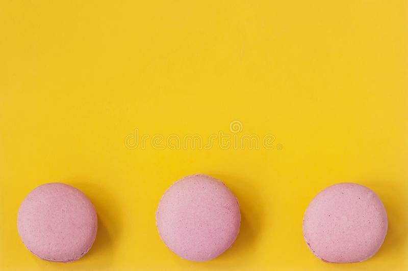 Three macaroons of pink color on yellow background top view download three macaroons of pink color on yellow background top view romantic morning negle Choice Image