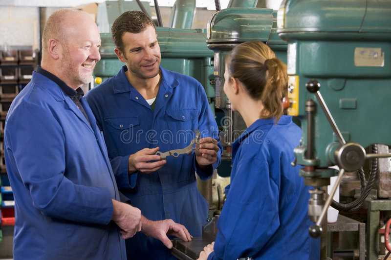 Three machinists in workspace by machine talking.  stock photo