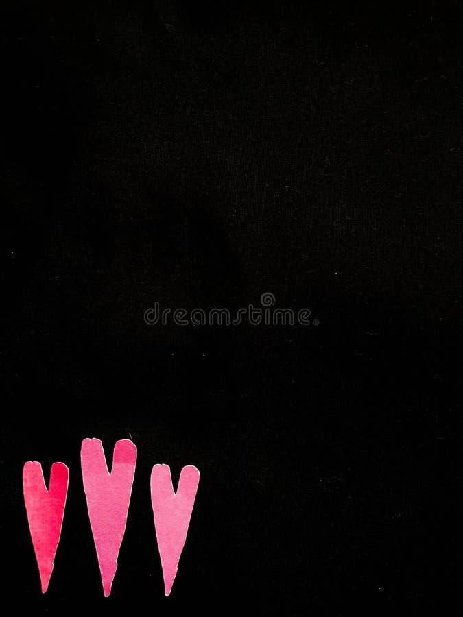 Three Magenta Hearts on Black Background royalty free stock image