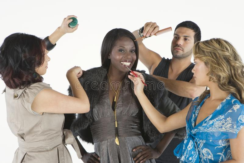 Three Makeup Artists Assisting Model royalty free stock photo