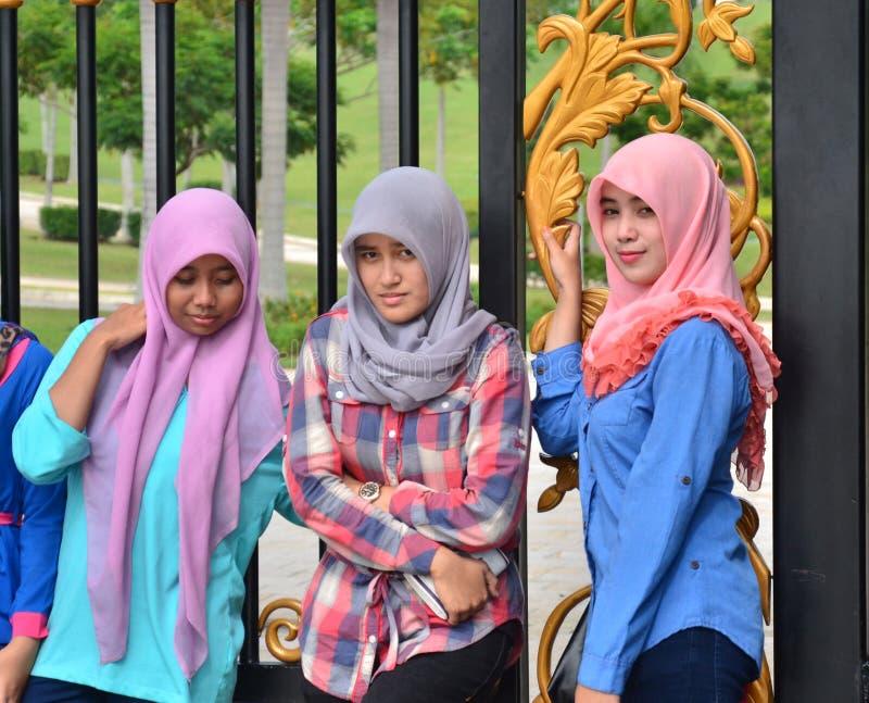 Three Malaysian girls wearing headscarves - Stock Image stock images