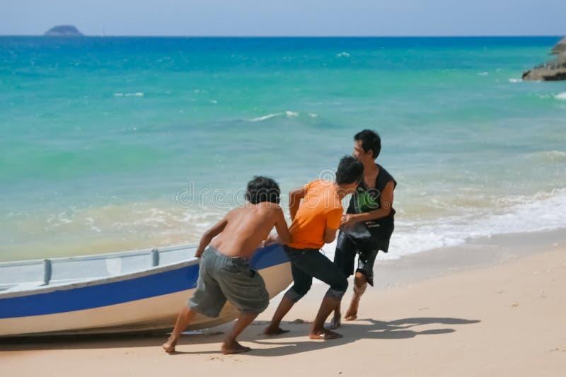 Three Malaysian man handlin their jetboat on tropical beach royalty free stock photos