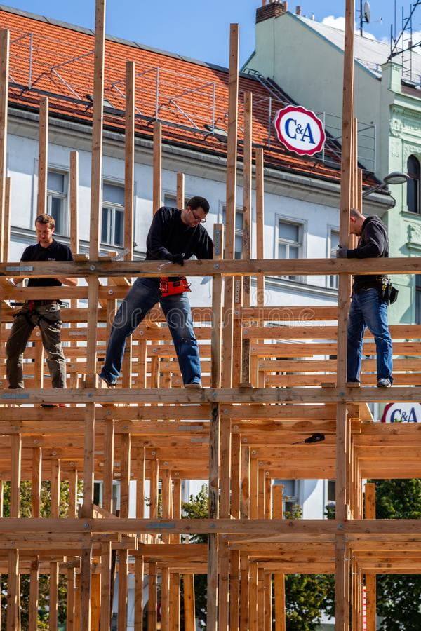 Three male carpenters building a wooden frame structure in Prague. royalty free stock photography