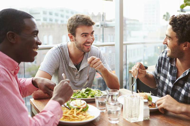 Three Male Friends Enjoying Lunch At Rooftop Restaurant stock images