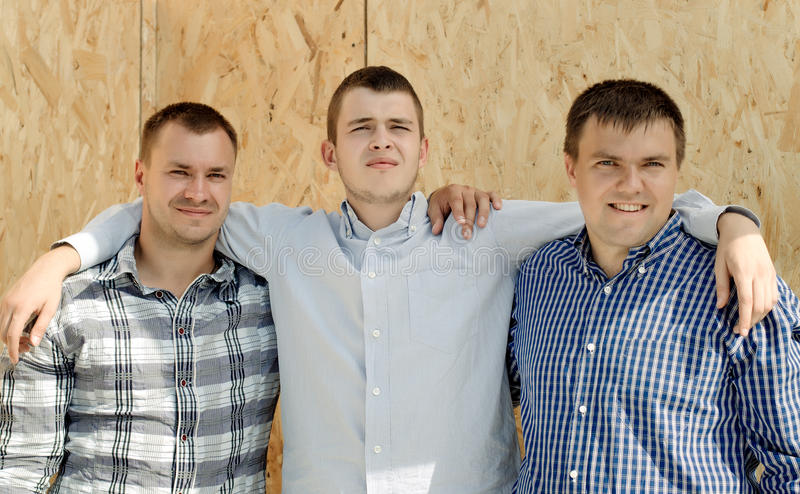 Three male friends standing arm in arm. Front wooden wall panel smiling happily camera they enjoy camaraderie together royalty free stock photos