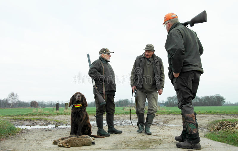Three male hunters and dog with hares. low perspective. Rural area. Winter season. Proud hunting dog sitting with the catch. royalty free stock photo