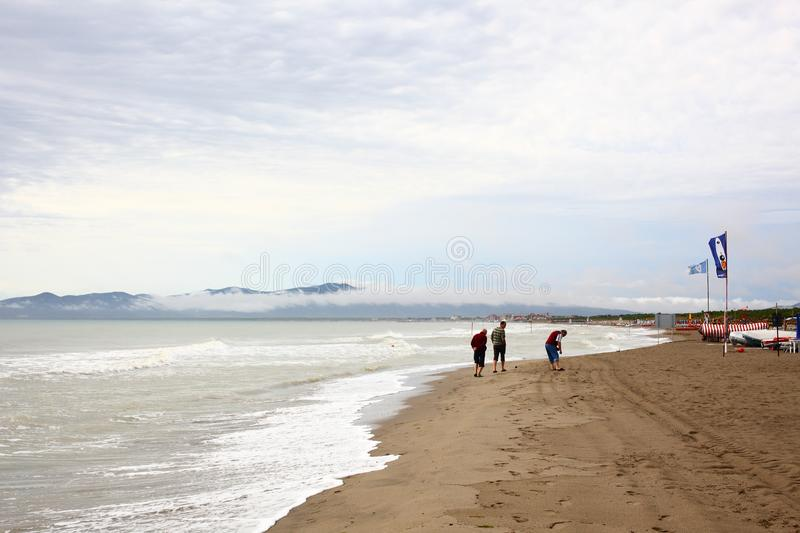 Grosseto, September 13 2017, Italy: three man walking on the beach after the storm on the coast royalty free stock image