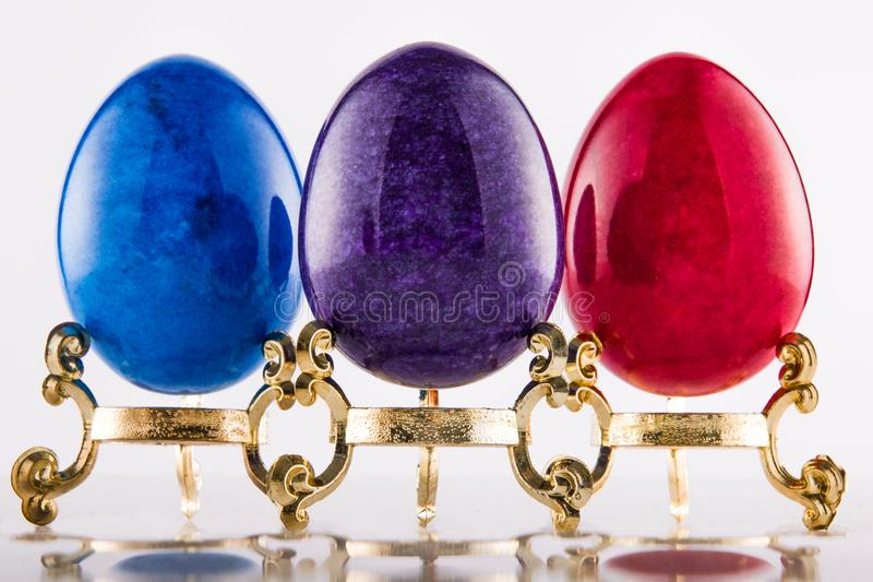 Three marble textured stone easter eggs on gold stands for eastern holiday in purple, blue and red. royalty free stock images