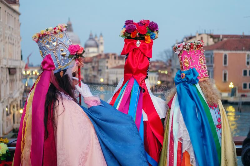 Three masked and dressed up women. On the bridge are looking  at Basilica Santa Maria Della Salute stock photos