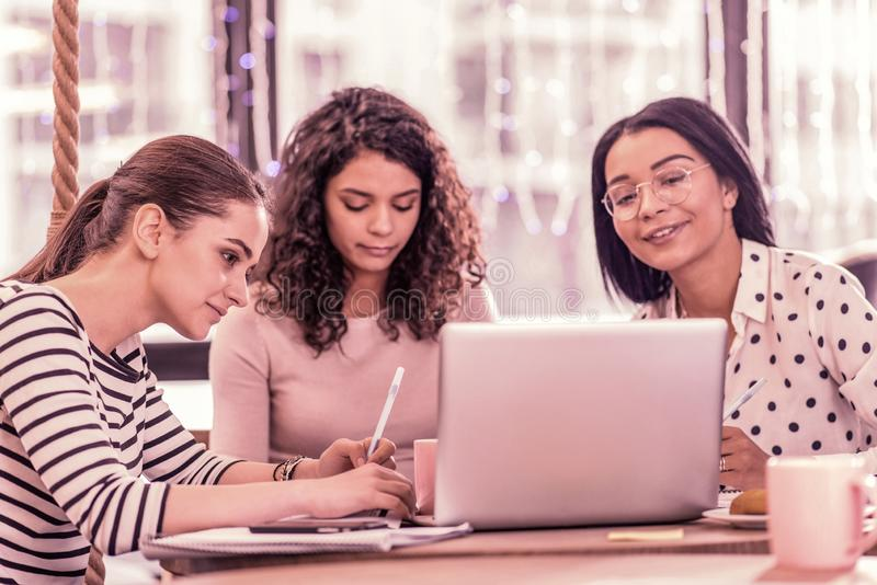 Three master students feeling busy while working on their project assignment royalty free stock images