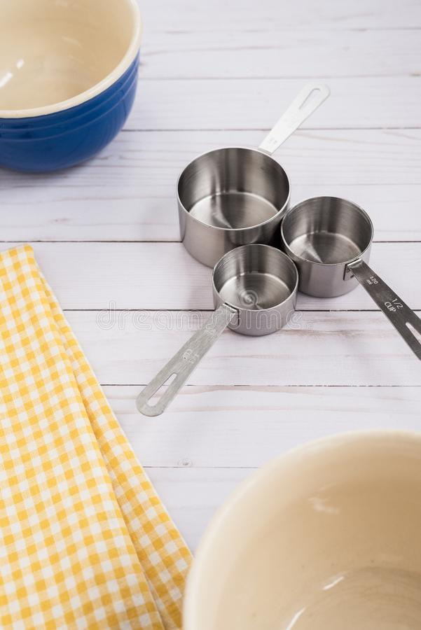 Three measuring cups and mixing bowls on a wood top royalty free stock image