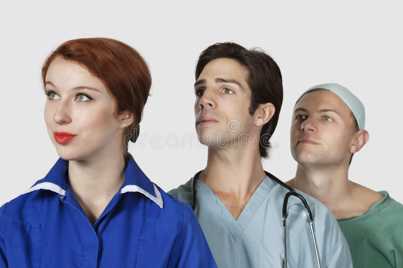 Three medical practitioners looking away against gray background stock images