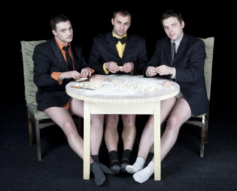 Three men. Without trousers round-table cook the dough royalty free stock images