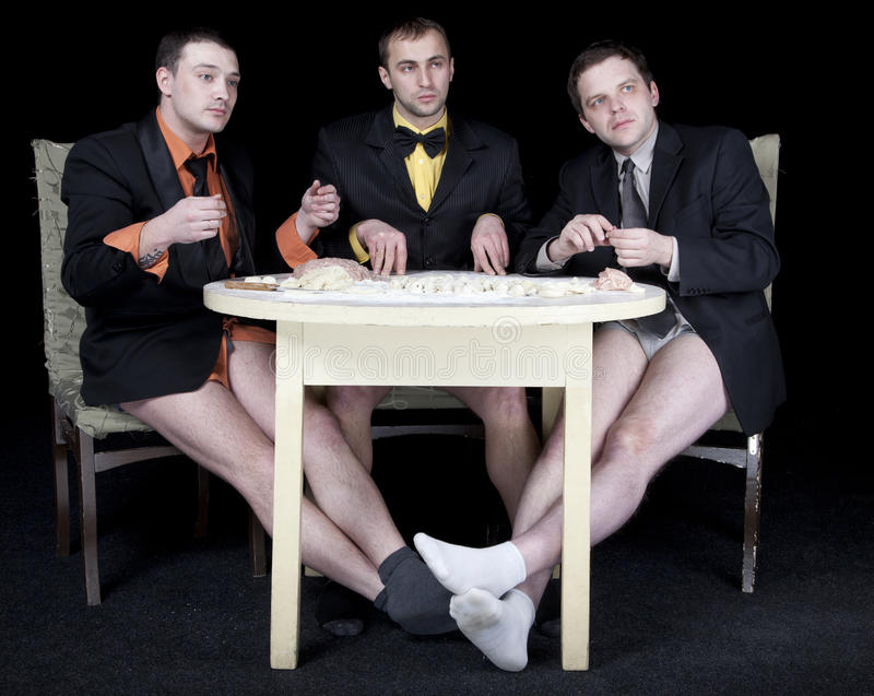 Three men. Without trousers round-table cook the dough stock photography