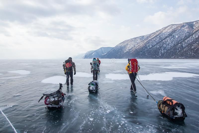 three men with backpacks going through ice water surface and hills on background, Russia, royalty free stock photography