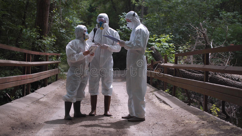 Three men in biohazard suits standing on a bridge stock photos