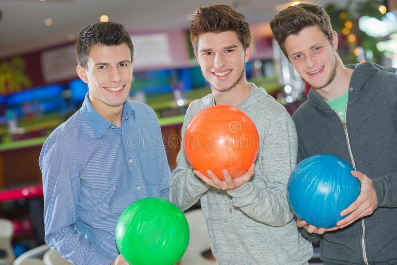 Three men with bowling balls stock image