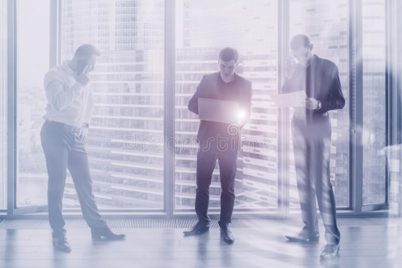 Three men discuss a business plan. stock images
