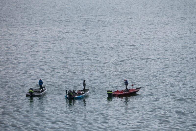 three men are fishing at the small motor boat in Kawaguchiko lake, Japan stock image