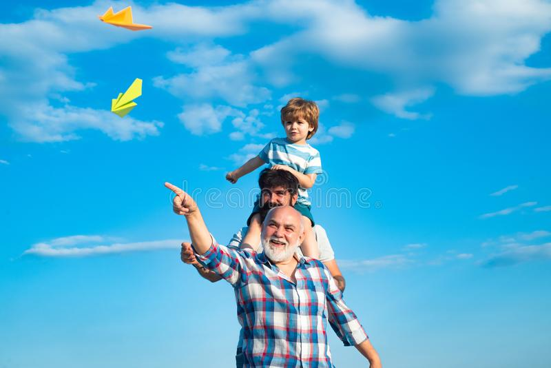 Three men generation. Cute son with dad playing outdoor. Fathers day - grandfather, father and son are hugging and stock photography