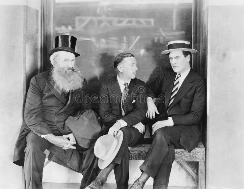 Three men sitting on a bench. (All persons depicted are no longer living and no estate exists. Supplier grants that there will be no model release issues royalty free stock photos
