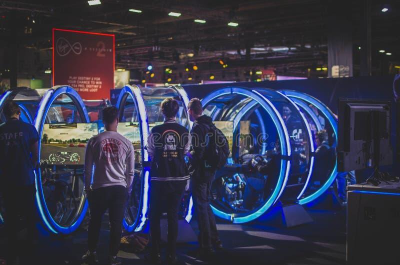 Three Men Standing in Front of Racing Arcade Machines stock photo