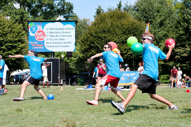 Three Men Throw In Unison At Outdoor Dodge Ball Game royalty free stock image
