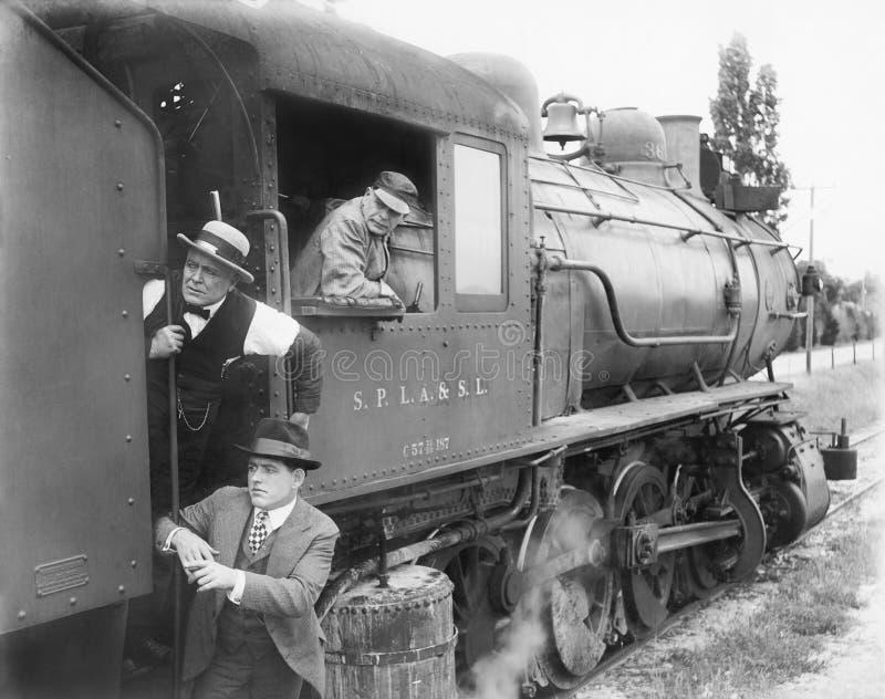 Three men waiting at a steam locomotive stock photo