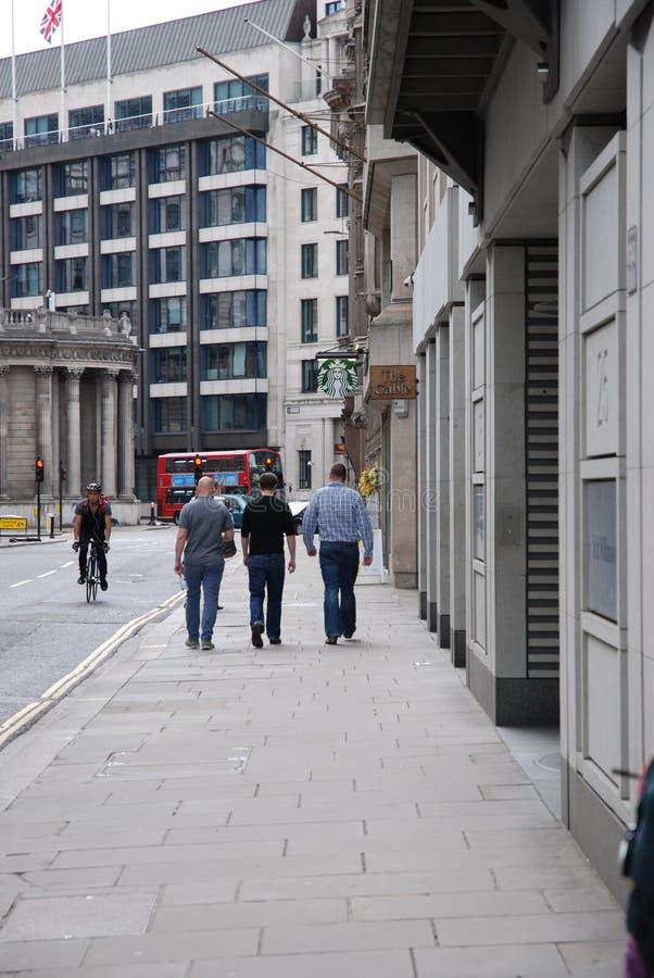 Three men walking royalty free stock images