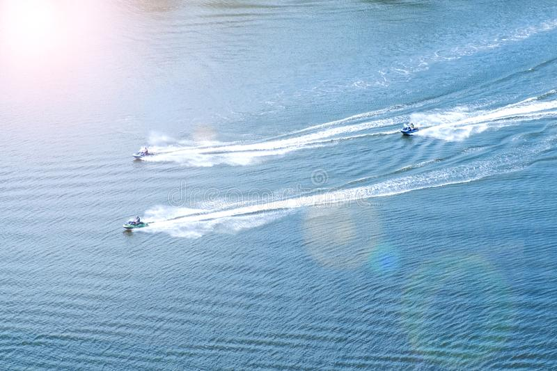 Three men on water scooters rush along the river in the rays of sunset sunlight against royalty free stock photo