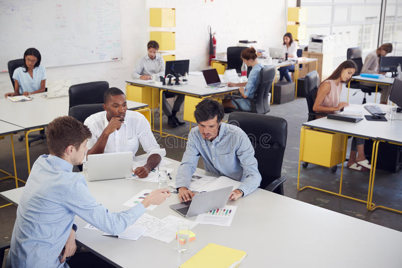 Three men working together in a busy office, elevated view royalty free stock photography