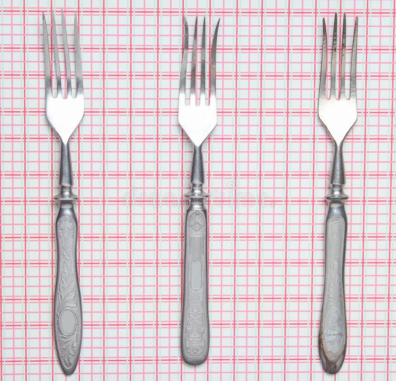 Three metal forks on a tablecloth. Top view. stock photos