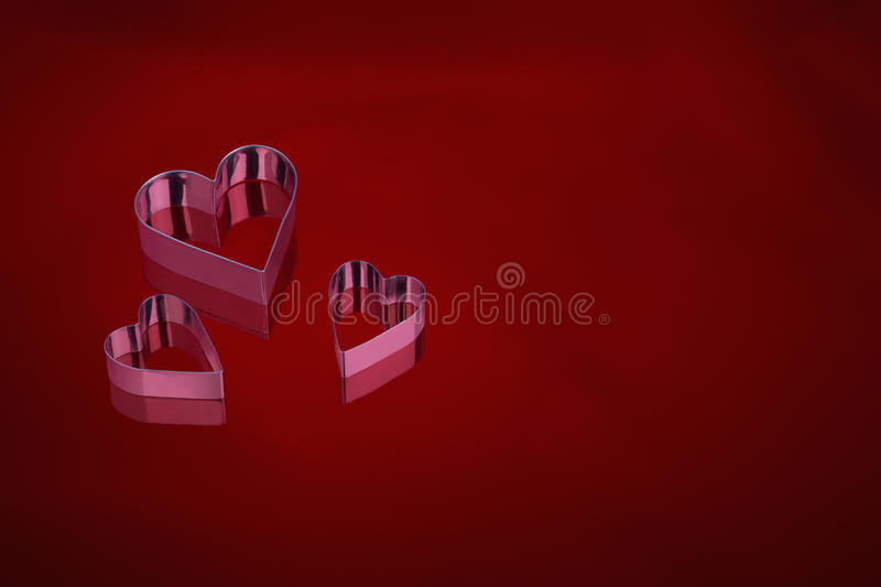 Three metal love hearts on a red background. Three metal love hearts on a dark red background stock image
