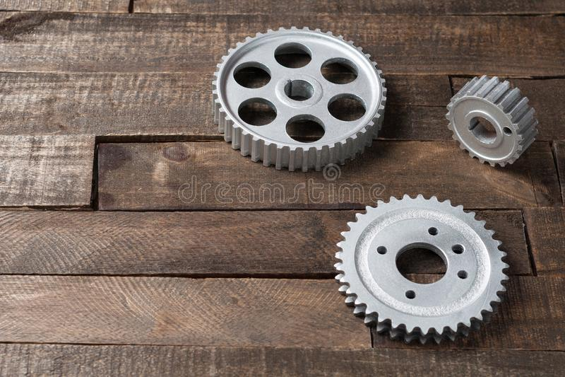 Three metal silver gears lies on old weathered wooden table in workshop stock photos