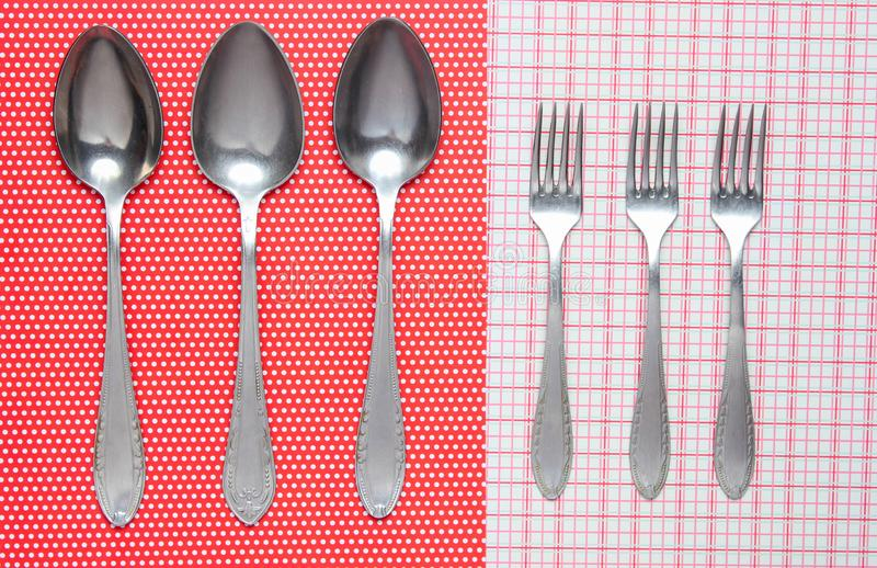 Three metal spoons and forks on a tablecloth. royalty free stock image